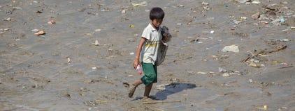 男孩收集在仰光河,缅甸的河岸的塑料瓶 库存照片