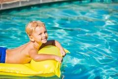 男孩放松和获得乐趣在黄色木筏的游泳池 库存照片