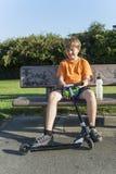 男孩放松在从骑马推挤滑行车的一条长凳 库存照片
