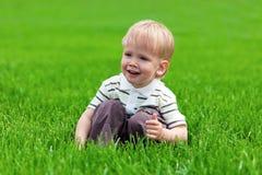 男孩新鲜的草一点坐的微笑 图库摄影