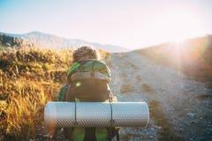 男孩旅游背包徒步旅行者步行ob晴朗的路 免版税库存图片