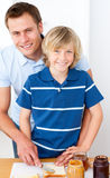男孩早餐父亲准备微笑的他的 免版税库存图片
