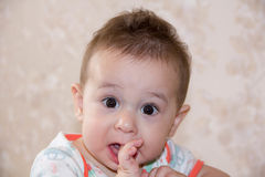男孩是哭泣和咬住您的手指,攀登第一颗牙 生长大的婴孩7个月 免版税库存照片