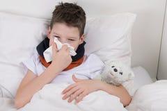 男孩是在床,他的喉头创伤上,他吹他的鼻子入纸一次性手帕 免版税库存图片