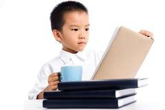 年轻男孩有一个杯子牛奶阅读书 库存照片