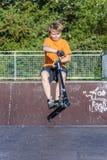 男孩有乐趣骑马推挤滑行车在冰鞋公园 库存照片