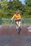 男孩有乐趣骑马推挤滑行车在冰鞋公园 库存图片