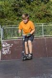 男孩有乐趣骑马推挤滑行车在冰鞋公园 免版税库存照片