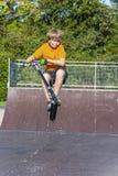 男孩有乐趣骑马推挤滑行车在冰鞋公园 免版税库存图片