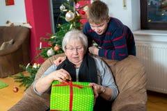男孩有他的祖母的一个圣诞节礼物 免版税库存图片