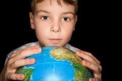 男孩查出的地球现有量保持在世界 库存图片