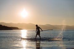 年轻男孩桨搭乘剪影在日落的 概念生活方式体育 免版税图库摄影