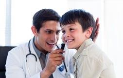 男孩检查一点s微笑的医生耳朵 免版税库存图片