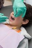 男孩检查了有的牙科医生新他的牙 免版税图库摄影