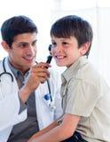 男孩检查英俊的小的s的医生耳朵 图库摄影