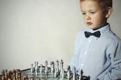 男孩棋使用 聪明的孩子 小天才孩子 聪明的比赛 棋枰 库存照片