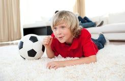 男孩楼层橄榄球位于的符合注意 免版税库存照片