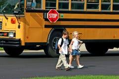 男孩横穿女孩街道 免版税图库摄影