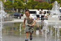 男孩横穿正方形由突然喷洒的喷泉击中了 库存照片