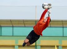 年轻男孩橄榄球或足球守门员跳游行 免版税图库摄影