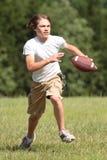男孩橄榄球运行中 免版税库存图片