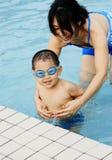 男孩母亲游泳 免版税库存照片