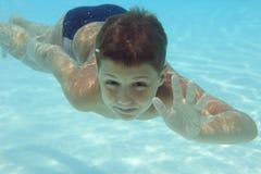 男孩水下池的游泳 免版税图库摄影