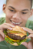 男孩汉堡吃少年 免版税库存图片