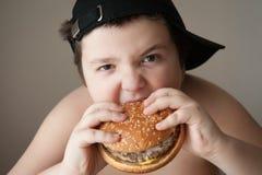 男孩汉堡吃 图库摄影