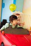 男孩汽车推进女孩玩具 库存图片