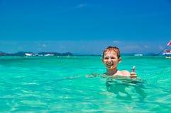 男孩沐浴在绿松石的10岁浇灌微笑热带海的孩子,当显示赞许时 与明亮的天空和海的海景 免版税库存照片