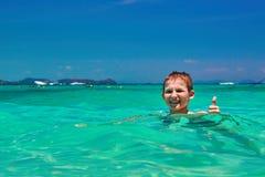 男孩沐浴在绿松石的10岁浇灌热带海 微笑的孩子,当显示赞许时 库存图片