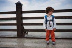 男孩沿一座桥梁走在公园 免版税库存照片
