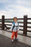 男孩沿一座桥梁走在公园 免版税图库摄影