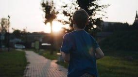 男孩沿江边跑反对凉快的日落的背景 令人惊讶的大气 凉快的英尺长度 股票视频