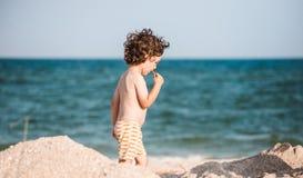 男孩沿沙滩走 库存照片