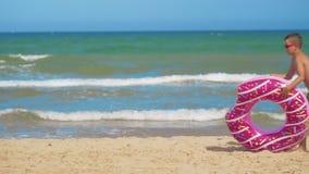 男孩沿海滩跑用一个桃红色可膨胀的多福饼,滚动它沿沙子以海为背景 影视素材