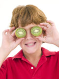 男孩注视拿着在年轻人的一半猕猴桃 免版税图库摄影
