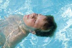 男孩浮动的池 库存照片