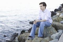 男孩海洋岩石坐少年 库存照片