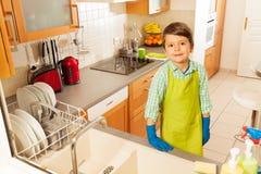 男孩清洗了在厨房水槽的所有盘 库存图片