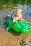 男孩游泳在有可膨胀的鳄鱼的河 免版税库存照片