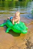 男孩游泳在有可膨胀的鳄鱼的河 库存图片