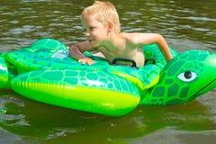 男孩游泳在有可膨胀的tur的河 库存图片