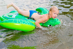 男孩游泳在有可膨胀的tur的河 免版税库存图片