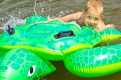 男孩游泳在有可膨胀的tur的河 库存照片