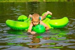 男孩游泳在有可膨胀的tur的河 免版税库存照片
