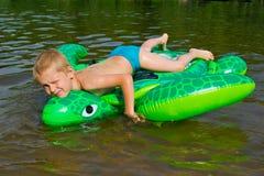 男孩游泳在有可膨胀的tur的河 免版税图库摄影