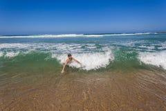 男孩游泳Shorebreak波浪 免版税库存照片