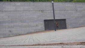 男孩溜冰板者在沿灰色城市墙壁的一个委员会慢慢地移动 股票录像